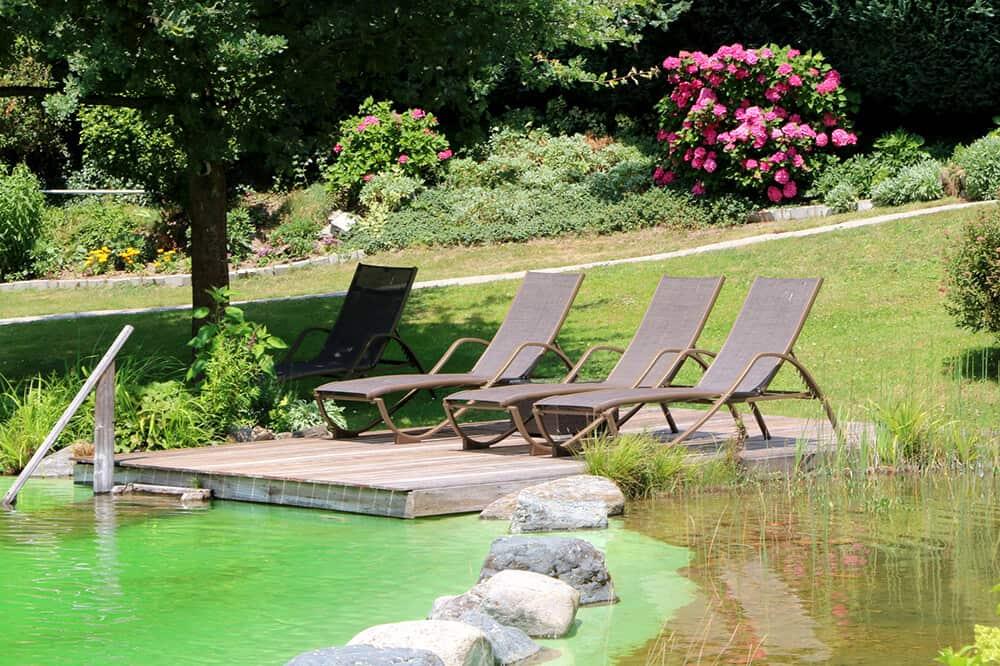 Schwimmteich im Garten mit Steinbegrenzung