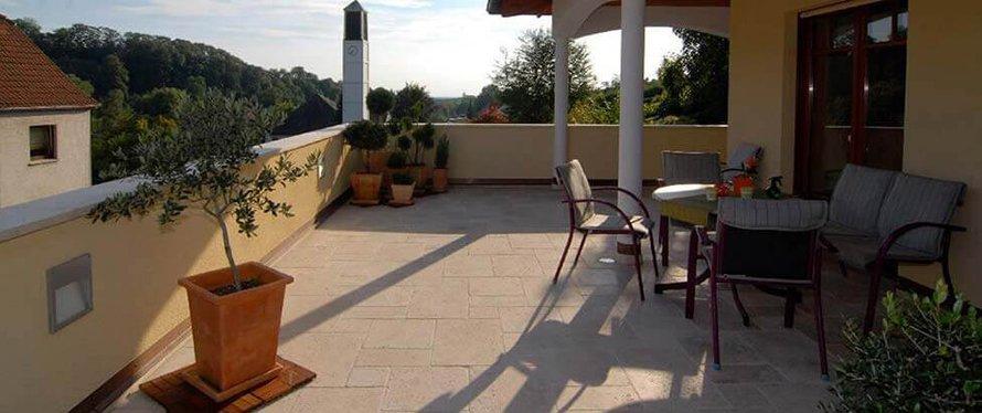 Mediterrane Details harmonieren perfekt zu Naturstein auf der Terrasse