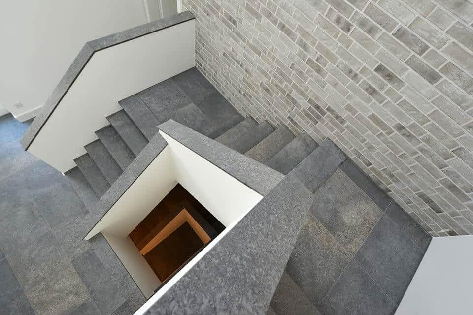 Steintreppe mit Richtungswechsel und Wandverkleidung aus verschiedenem Stein