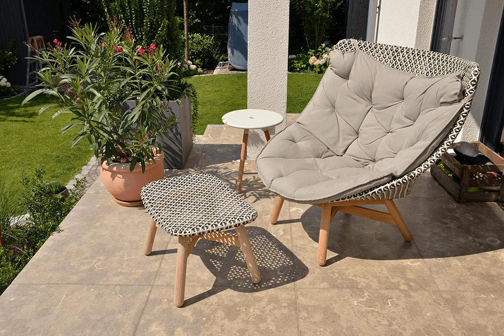 Terrasse aus Natursteinplatten mit Möbeln